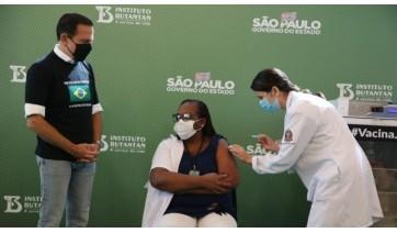 A enfermeira Mônica Calazans recebeu a primeira dose da vacina, aplicada pela também enfermeira Jéssica Pires de Camargo, observadas pelo governador João Dória (Imagem: GovSP).